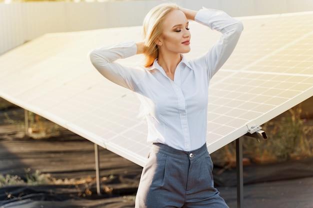 Dziewczyna stoi i patrzy w prawo, w pobliżu rzędów paneli słonecznych na ziemi ze światłem słonecznym
