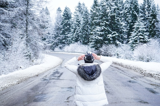 Dziewczyna stoi na bezludnej drodze wokół wysokich drzew, z bliska. ludzie na zimowej drodze. marzenia o podróży. wycieczka zimowa