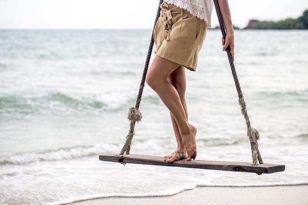 Dziewczyna stoi na huśtawce na plaży w tajlandii