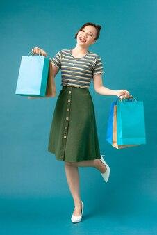 Dziewczyna stoi na jednej nodze i po zakupach trzyma w rękach zakupy