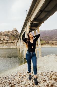 Dziewczyna stoi na nabrzeżu z widokiem na górskie jezioro turano i wioskę