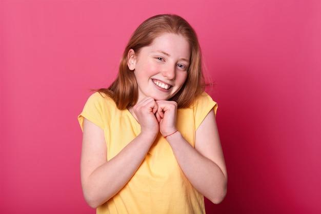 Dziewczyna stoi na różowej ścianie, ubrana na co dzień żółta koszulka, ma długie jasne włosy, trzyma obie ręce pod brodą