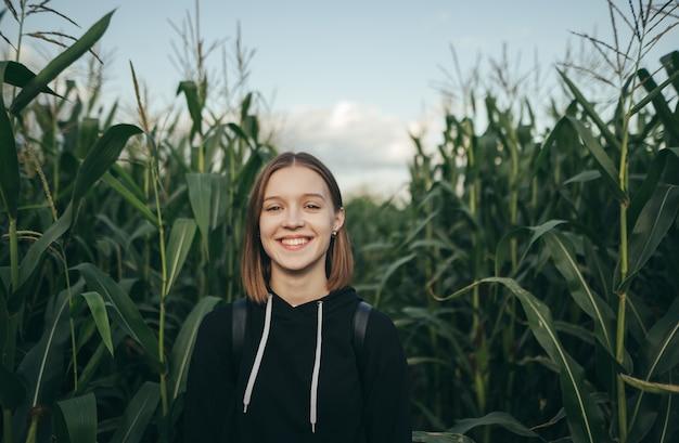 Dziewczyna stoi na tle pola kukurydzy, patrzy w kamerę i uśmiecha się