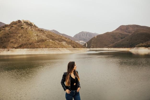 Dziewczyna stoi na wzgórzu.