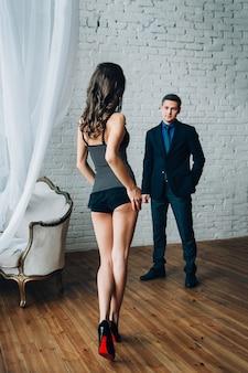 Dziewczyna stoi przed facetem, facet patrzy na nią