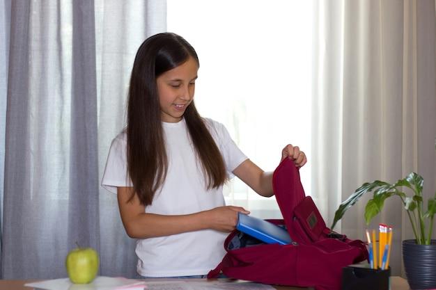 Dziewczyna stoi przy stole w domu i chodząc do szkoły wkłada zeszyty do szkolnego plecaka