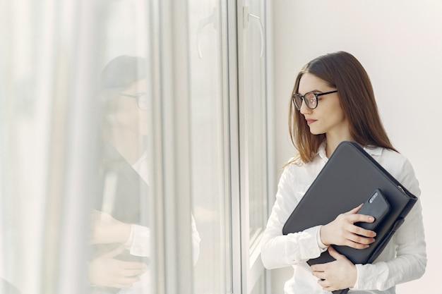 Dziewczyna stoi w biurze z folderu