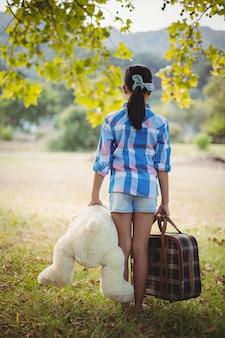 Dziewczyna stoi w parku z misiem i walizki