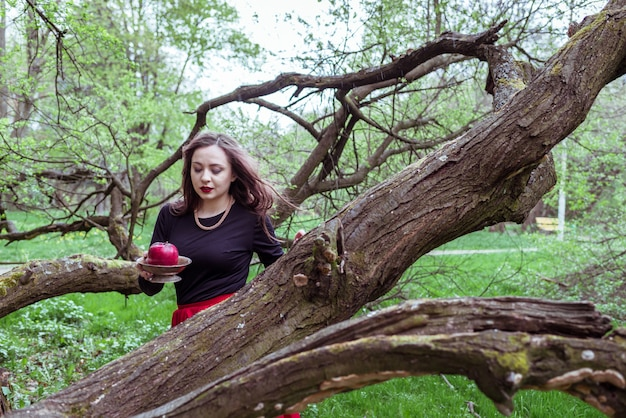 Dziewczyna stoi w pobliżu pnia drzewa