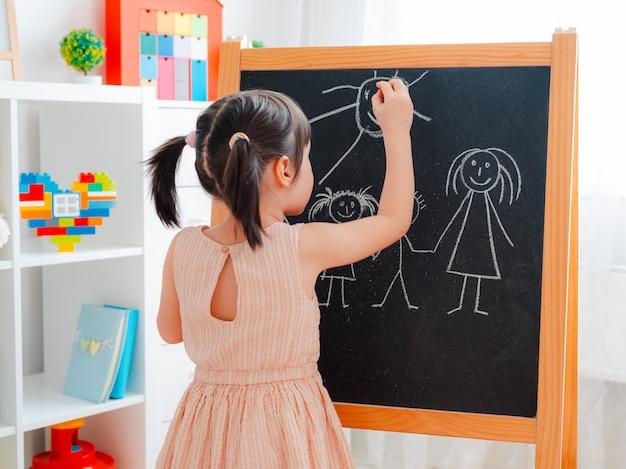 Dziewczyna stoi w pokoju dziecięcym z tablicą i rysuje rodzinę kredą.