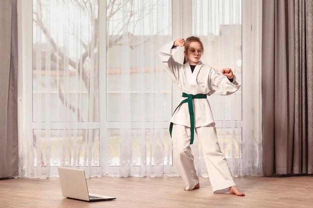 Dziewczyna stoi w stojaku do walki przed laptopem