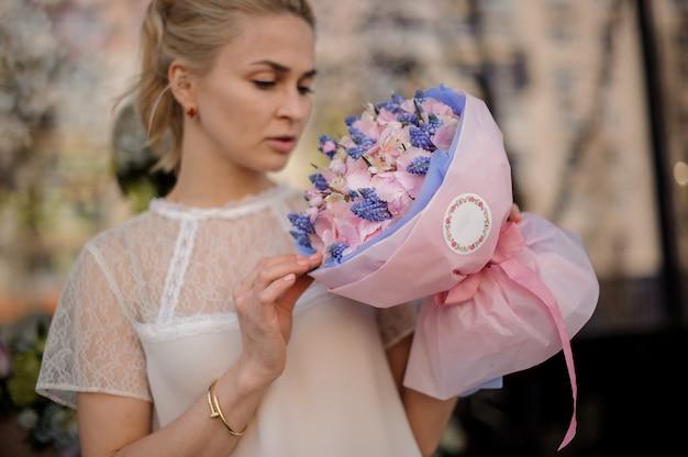 Dziewczyna stoi z bukietem różowych i niebieskich kwiatów