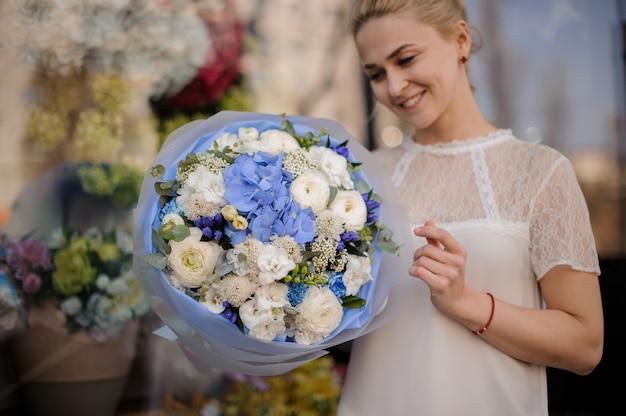 Dziewczyna stoi z bukietem z białymi i niebieskimi kwiatami