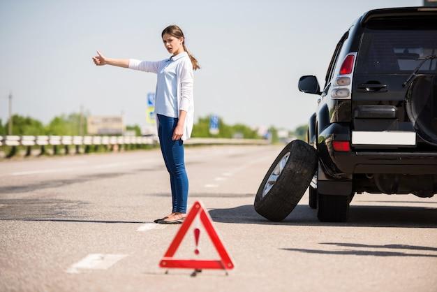 Dziewczyna stoi z podniesioną ręką i łapie przejeżdżający samochód.