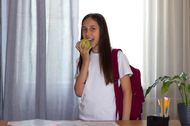 Dziewczyna stoi ze szkolnym plecakiem w domu przy stole i zjada jabłko z powrotem do koncepcji szkoły