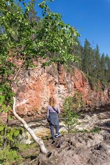Dziewczyna stojąca na skale nad wzburzoną rzeką, finlandia. park narodowy oulanka