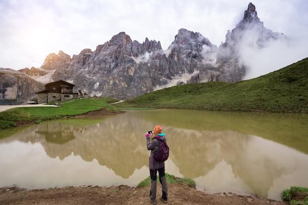 Dziewczyna stojąca nad jeziorem i robiąca zdjęcie