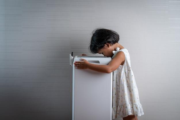 Dziewczyna stojąca oddychająca przy oczyszczaczu powietrza w pomieszczeniu