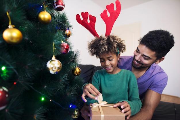Dziewczyna stojąca przy choince w objęciach ojca i rozpakowująca prezent