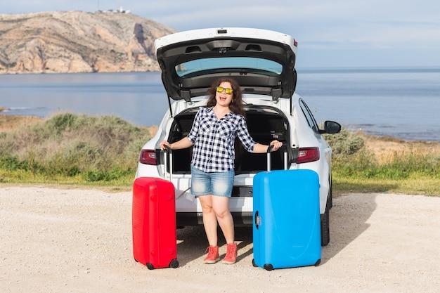 Dziewczyna stojąca w pobliżu tyłu samochodu, uśmiechając się i przygotowując się do drogi. letnia wycieczka samochodowa.