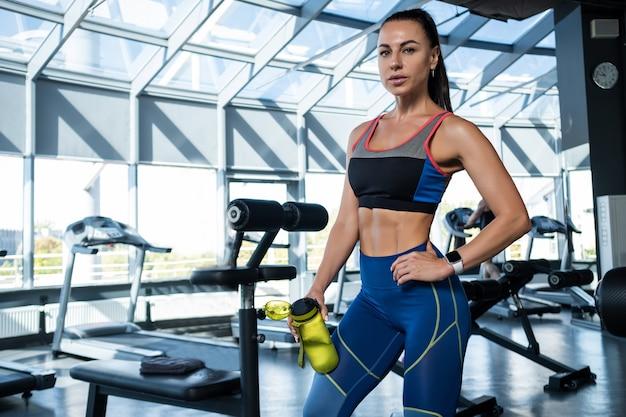 Dziewczyna stojąca z bidonem na siłowni po treningu