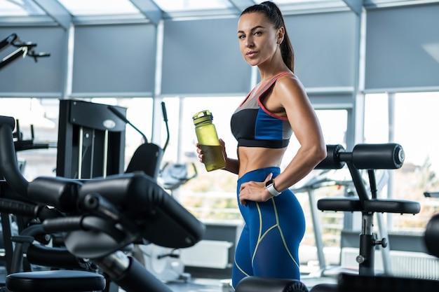 Dziewczyna stojąca z bidonem po treningu na siłowni