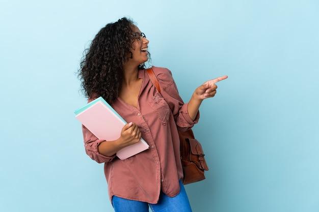 Dziewczyna student na białym tle na niebieski palec wskazujący z boku i prezentacji produktu