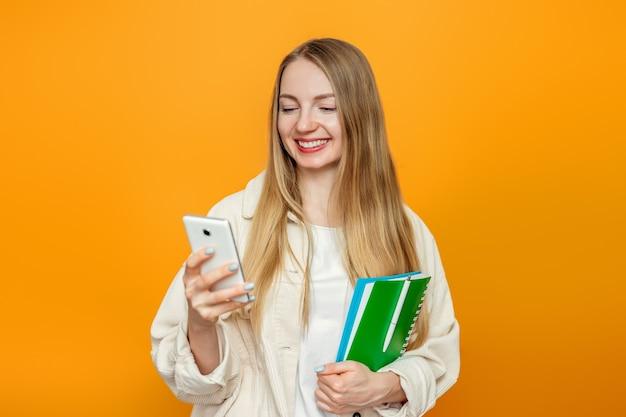 Dziewczyna student patrząc na ekran telefonu i uśmiechając się