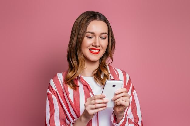 Dziewczyna student patrzy na ekran telefonu komórkowego i czyta wiadomości. freelancer młoda kobieta w czerwonej koszuli w paski