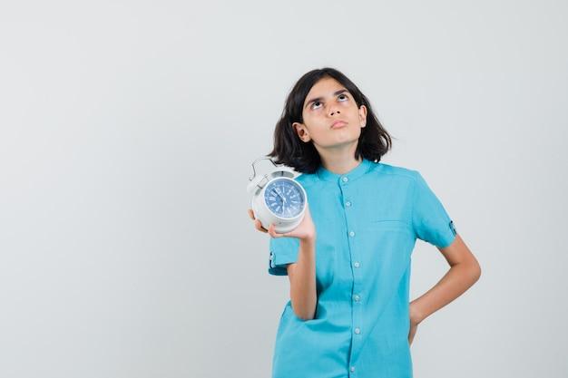 Dziewczyna student pokazuje zegar myśląc w niebieskiej koszuli i patrząc skoncentrowany.