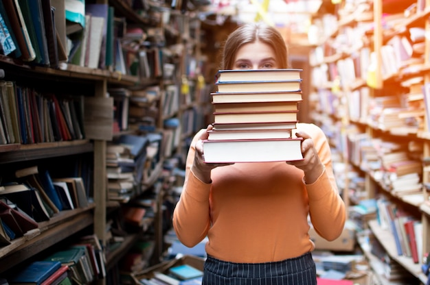 Dziewczyna student posiada stos książek w bibliotece