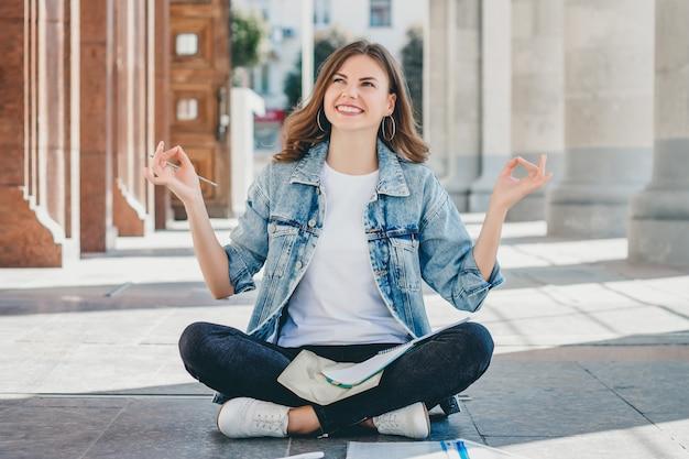 Dziewczyna student siedzi na podłodze i medytacji. urocza dziewczyna prosi o dobrą ocenę na egzaminie. dziewczyna modli się w pozycji lotosu.