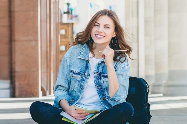 Dziewczyna student siedzi w pobliżu uniwersytetu i uśmiecha się.