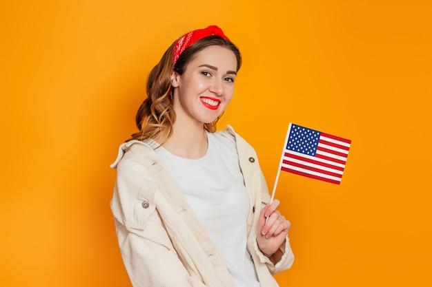 Dziewczyna student trzyma małą amerykańską flagę i uśmiecha się na białym tle na pomarańczowym tle