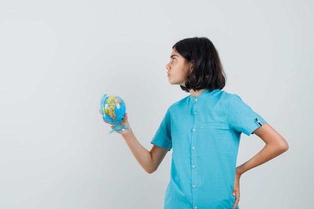 Dziewczyna student trzyma mini kulę ziemską, patrząc z boku w niebieskiej koszuli i patrząc skoncentrowany