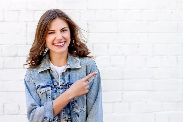 Dziewczyna student wskazuje palcem na ścianę. dziewczyna pokazuje palec wskazujący na tle