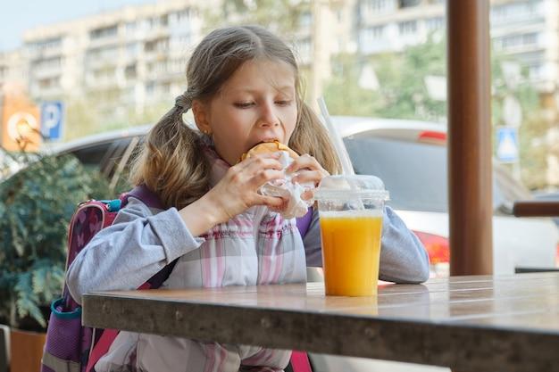 Dziewczyna student z plecakiem, jedzenie burgera z sokiem pomarańczowym