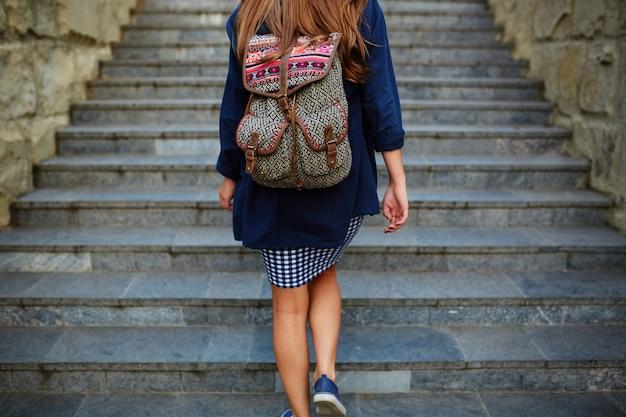 Dziewczyna student z plecakiem, wchodzenie po schodach