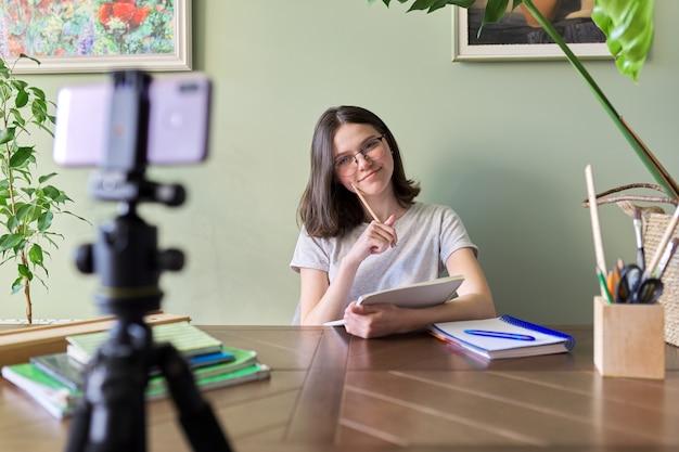 Dziewczyna studentka nastolatka ucząca się online za pomocą smartfona, wideokonferencji, wideorozmów, edukacji na odległość, uczenia się w domu