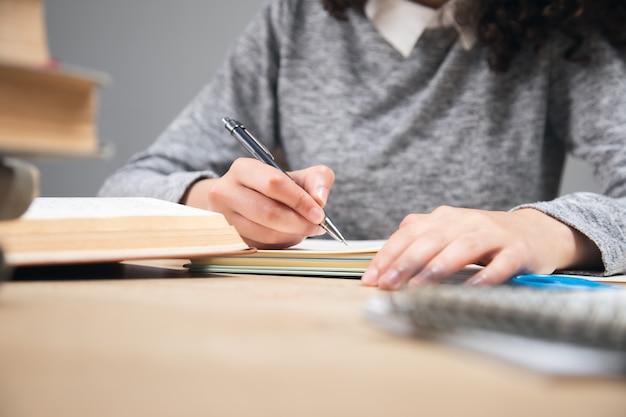Dziewczyna studentka pisząca w notatniku ze stosem książek
