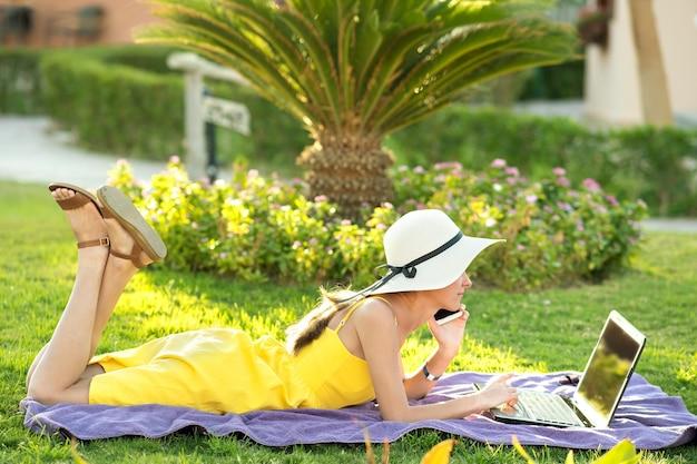Dziewczyna studentka w żółtej letniej sukience odpoczynku na zielonym trawniku w parku latem studiując na komputerze laptop o rozmowie na telefon komórkowy