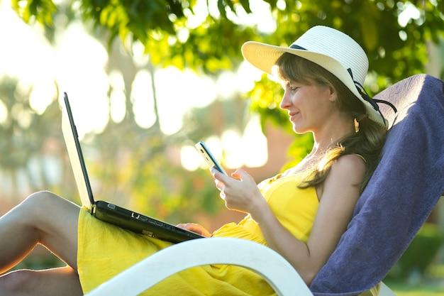 Dziewczyna studentka w żółtej letniej sukience odpoczynku na zielonym trawniku w parku latem studiując na komputerze laptop sms-y na telefon komórkowy.