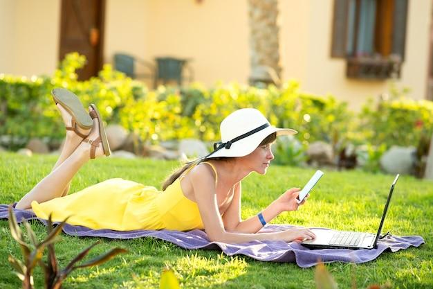 Dziewczyna studentka w żółtej letniej sukience odpoczywająca na zielonym trawniku w letnim parku studiuje na komputerze