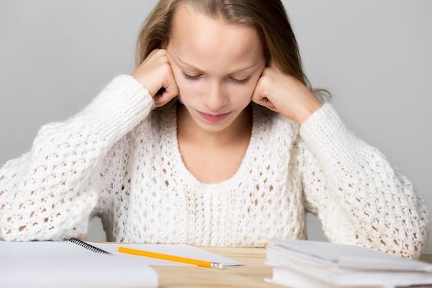 Dziewczyna studiuje na drewnianym stole