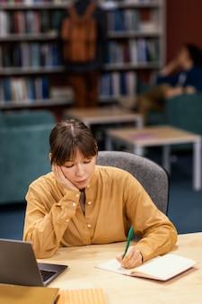Dziewczyna studiuje w bibliotece uniwersyteckiej