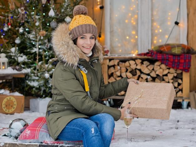 Dziewczyna świętuje boże narodzenie na zewnątrz. świąteczny taras z udekorowaną choinką i s