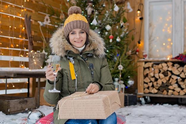 Dziewczyna świętuje boże narodzenie na zewnątrz. świąteczny taras z udekorowaną choinką i śniegiem.