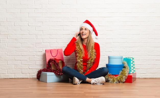 Dziewczyna świętuje boże narodzenie wakacje z boże narodzenie kapeluszem i wiele prezenty opowiada mobilny