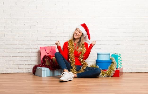 Dziewczyna świętuje zwycięstwo z boże narodzenie kapeluszem i wiele prezenty świętuje boże narodzenie wakacje