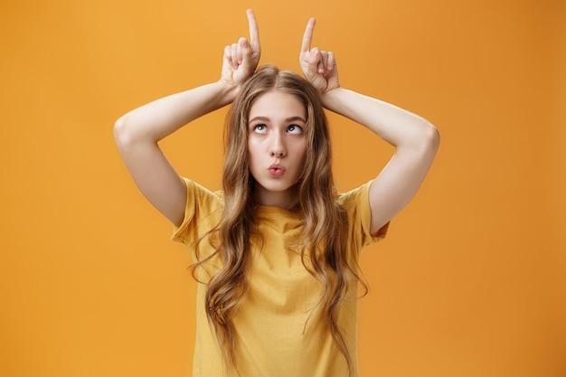 Dziewczyna szaleje z nudów, robiąc dziwaczne, zabawne miny, wygłupiającą się, mrużąc oczy, trzymając palce wskazujące na głowie jak rogi wystające język i składane usta małpujące na pomarańczowym tle.